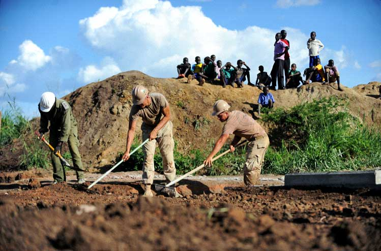 AROMA, Uganda - Local residents of Aroma, Uganda look on as service members from the U.S. Naval Mobile Construction Battalion-11, Combined Joint Task Force-Horn of Africa, grade the area surrounding the Walela Cultvert Bridge on May 5, 2009. This was the final construction phase of a bridge that connects the main Lira road to the Aroma sub-county. Funded by Combined Joint Task Force - Horn of Africa, the Walela Bridge was constructed by 25 U.S. Navy construction engineers in partnership with their counterparts from the Uganda People's Defense force. It will improve the lives of more than 60,000 people from three villages by enhancing their transportation ability, providing them with year-round access to the Lira market, and aiding in the delivery of humanitarian assistance supplies. (Photo by Technical Sergeant Dawn Price, CJTF-HOA)
