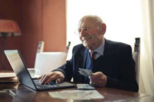 positive senior businessman typing on laptop while holding money in hand