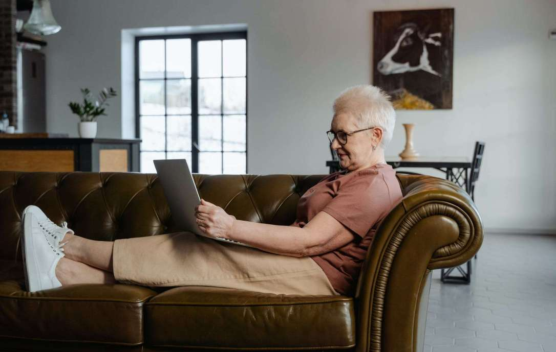 woman sitting on a leather couch using a laptop
