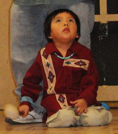 Hopi child holding drum stick and keeping rhythm with his family who is performing a song. This represents the raft attention of a child and learning by observing.