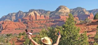 Woman with arms lifted up facing Sedona red cliffs; signifies one of the sites where we do Sedona sunrise ceremony or sunset ceremony and connect with ancestor wisdom.