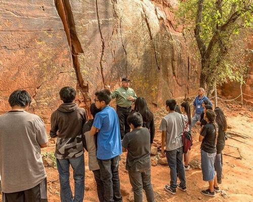 Hopi high school students viewing rock art site depicts one of the projects co-sponsored by Crossing Worlds Hopi Projects several times.