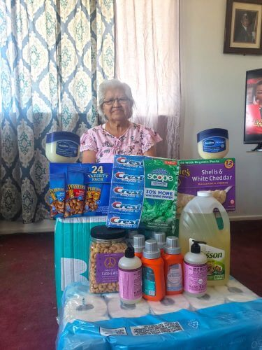 Hopi elder receives a coronavirus emergency hygiene and food supply box shipped by Crossing Worlds Hopi Projects. She has displayed the toilet paper, cleaning, toiletry and food items in front of her.