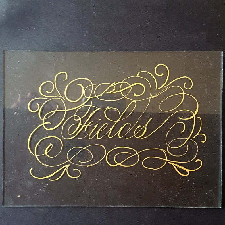 Practice run of gold ink on glass for bridal table calligraphy piece.
