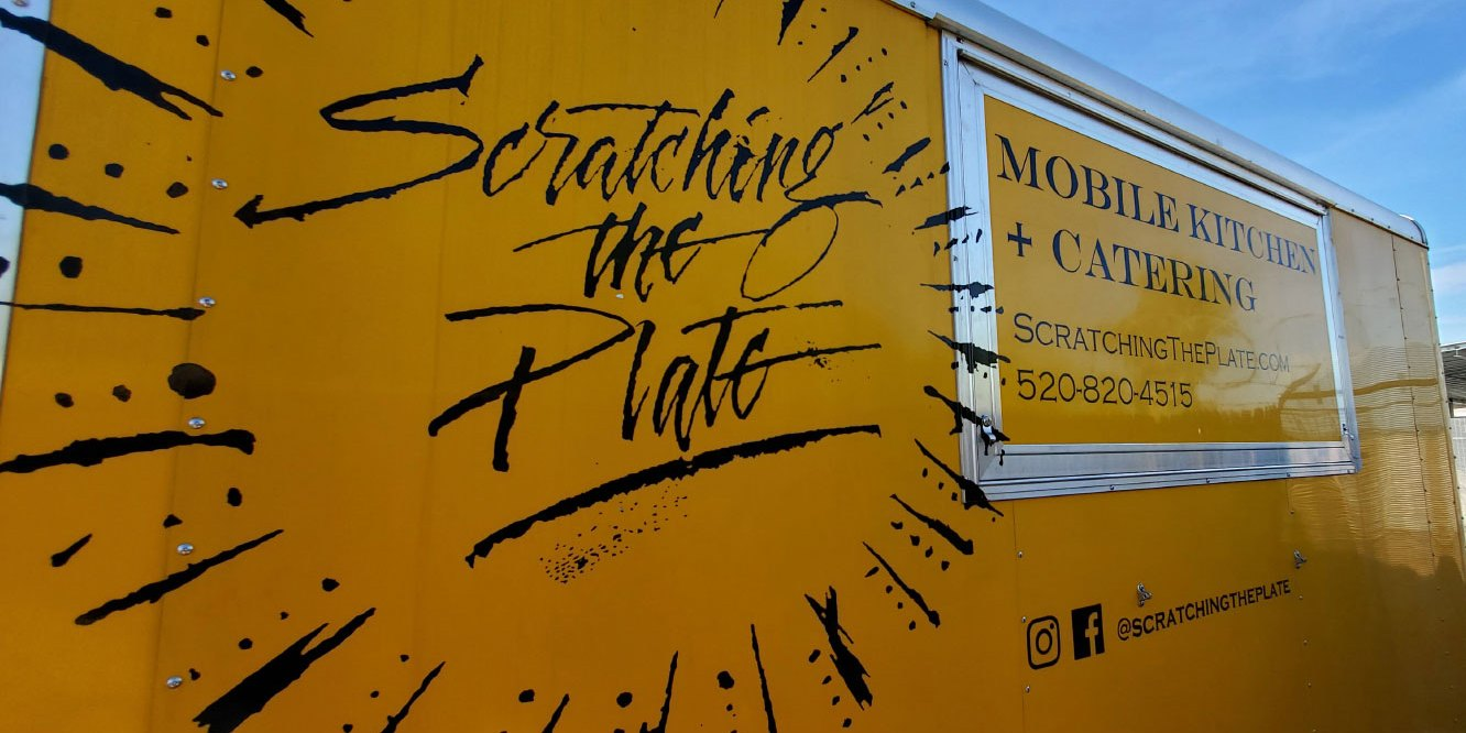 Hand Painted Logo in black paint on a yellow catering trailer for Scratching the Plate