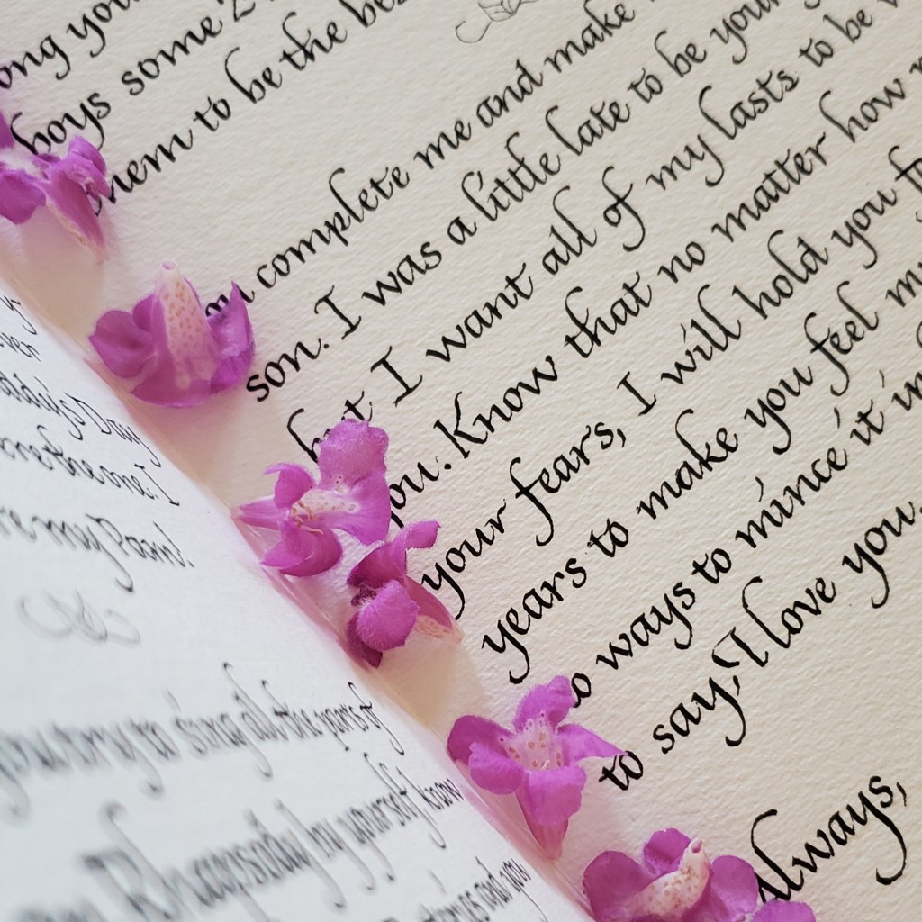 Black Italic calligraphy on white textured paper with a fold in it. Along the fold are small purple flowers.