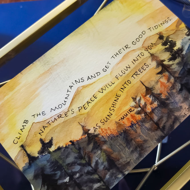 A watercolor painting of the sun rising over a forest with a John Muir quote written on the skyline.