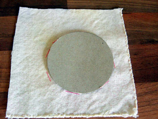 Place the cardboard circle onto the fabric.