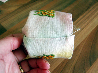 Sewing the seams to close the tin.