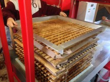 A sheet of wooden slats is placed over the blanket full of mash and the process is repeated.