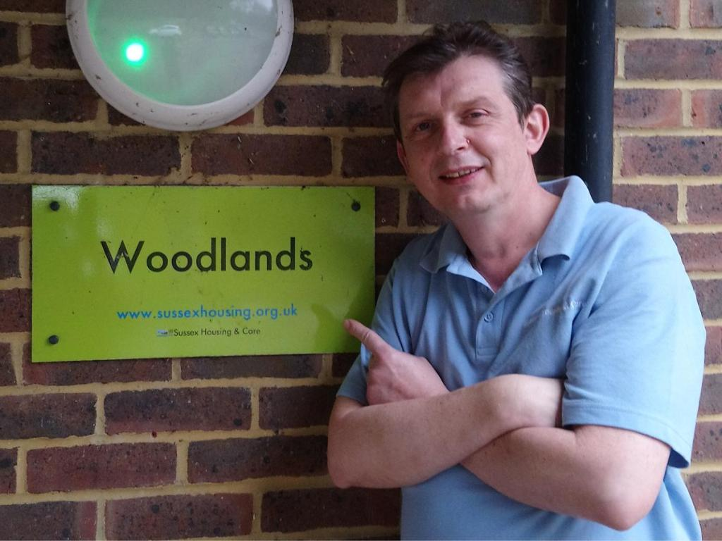 "Christian Rose photographed adjacent to a ""Woodland"" Sussex Housing & Care sign."