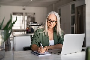 Senior stylish woman taking notes in notebook while using laptop