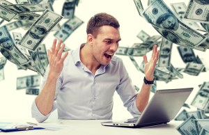 angry man in front of laptop with dollar bills on the background