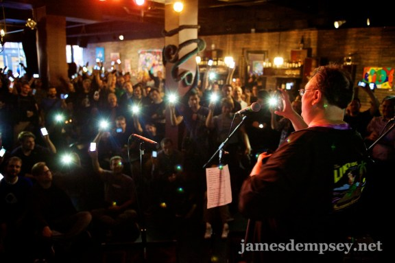 James Dempsey takes a photo of the full-house crowd raising their iPhones high