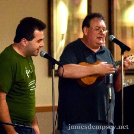 Matt Smollinger singing at microphone with James Dempsey playing ukulele