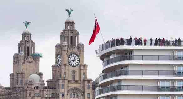 Cunard Lines' Queen Elizabeth passes the Royal Liver Building and the Cunard Building (right) as their fleet gather together in spectacular fashion in Liverpool, its spiritual home, as the company marked its 175th anniversary. The historic lines' three ships, the largest passenger ships ever to muster together on the River Mersey, lined up just 130 metres apart in the river. Picture date Monday 25th May, 2015. Picture by Christopher Ison.