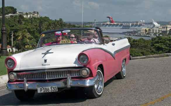 A Cuban taxi driver, piloting a vintage car, pulls up to the El Morro Castle while the Carnival Paradise cruise ship is docked in Havana, Cuba. (Andy Newman/Carnival Cruise Line)