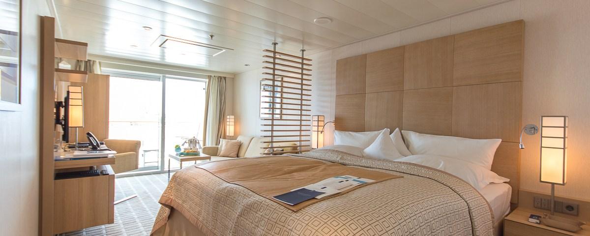 Ein großes Bett und eine gemütliche Sofaecke finden wir in der Veranda Suite an Bord der MS EUROPA 2