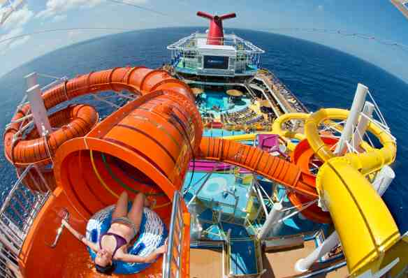 A guest onboard Carnival Vista slides down Kaleid-O-Slide, a water tube attraction situated amid WaterWorks, the ship's onboard water park. The largest and most innovative cruise vessel in Carnival Cruise Line's fleet, Carnival Vista measures 133,500 tons, 1,055 feet long and has a guest capacity of almost 4,000 passengers. Photo by Andy Newman/Carnival Cruise Line