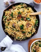 Cast iron skillet filled with spaghetti noodles, seared mushrooms and kale