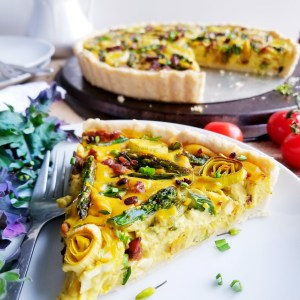 Asparagus, Leek and Tempeh Bacon Quiche in a tender Biscuit Crust sliced on white plate