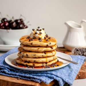 Vegan chocolate chip pancakes served in a stack with coconut whip and maple syrup