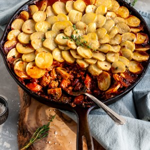 Vegan Savory Skillet Stew with Baby Potato Topping with a serving scooped out of the skillet