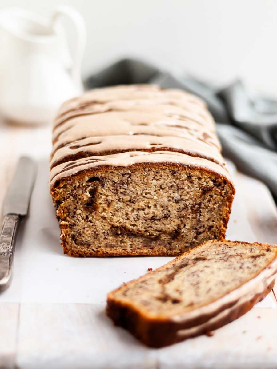Vegan Cinnamon Swirl Banana Bread glazed, with one slice made