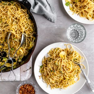 20 Minute Garlicky Breadcrumb Pasta with Shredded Brussels Sprouts being served from skillet onto white plates