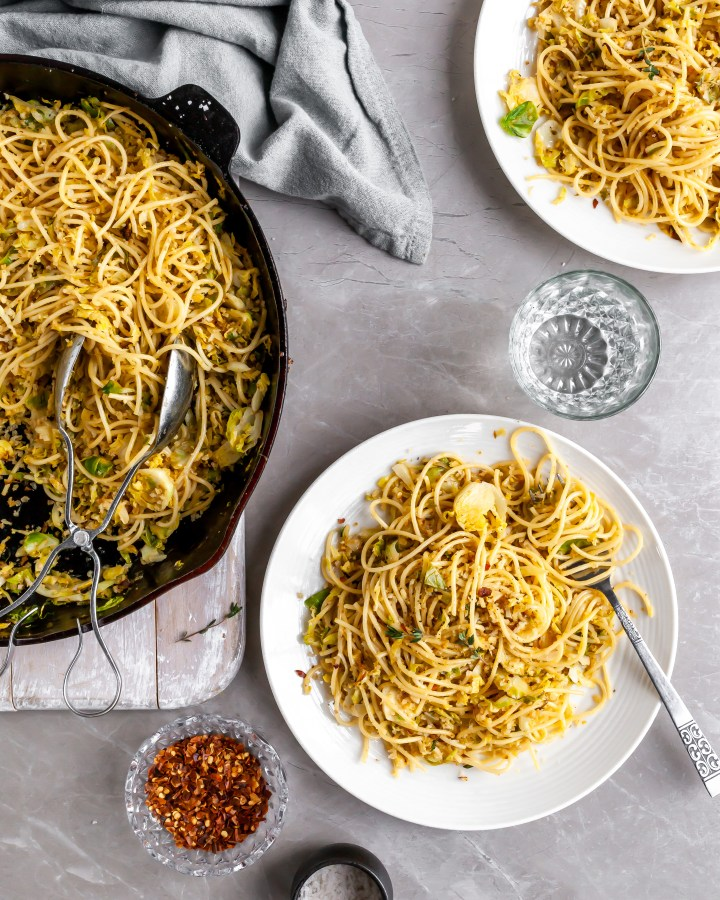15 Minute Garlicky Breadcrumb Pasta with Shredded Brussels Sprouts being served from skillet onto white plates