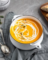 Creamy Curried Carrot, Ginger and Red Lentil Soup in pot with a swirl of coconut milk
