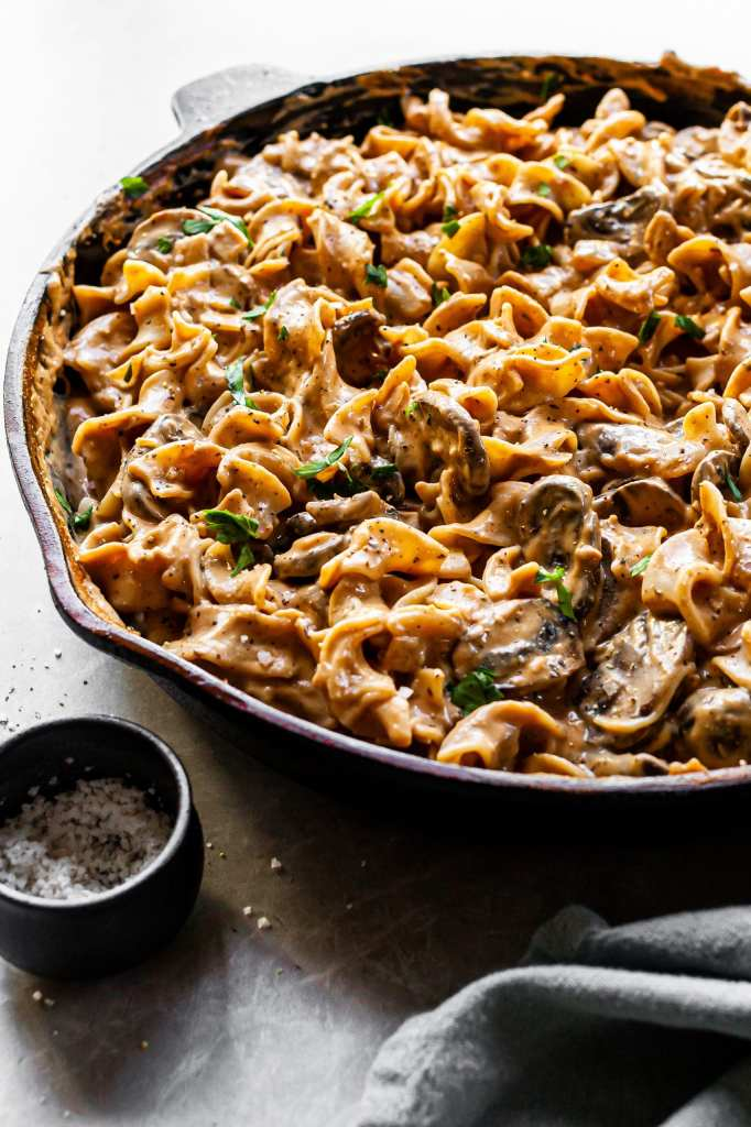 Side view of mushroom stroganoff in cast iron skillet, highlighting the creamy sauce