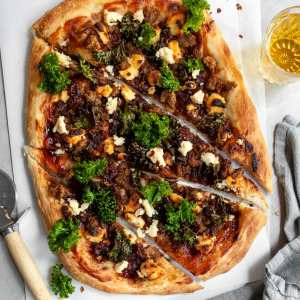 Vegan Caramelized Onion, Sausage and Kale Pizza with Almond Ricotta sliced and served with a glass of beer