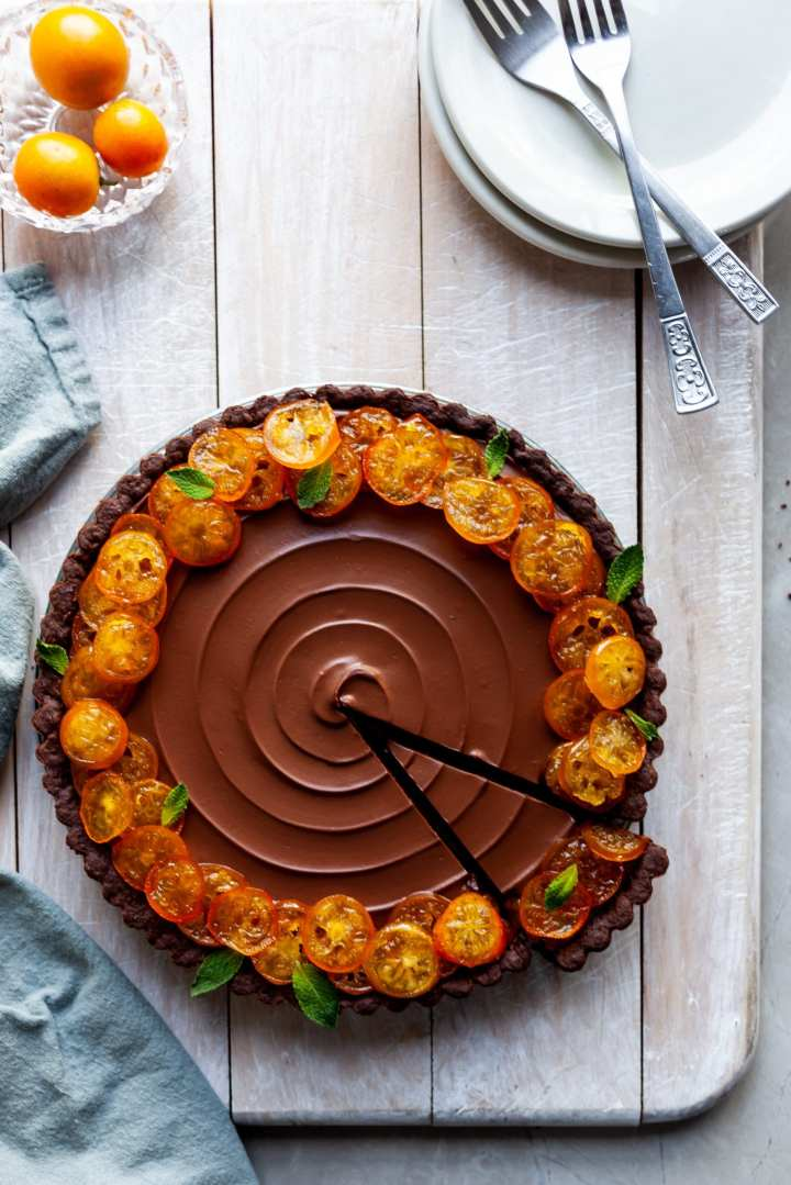Vegan Chocolate Orange Tart with Candied Kumquats with one slice ready to be served on a white plate