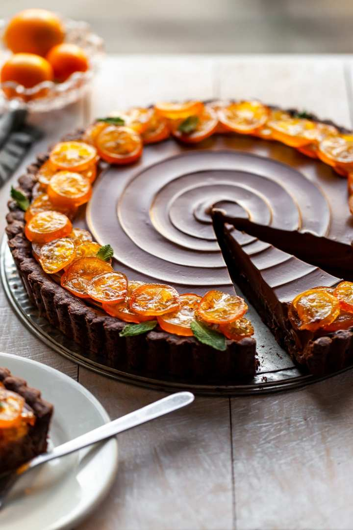 Vegan Chocolate Ornage Tart with Candied Kumquats with 2 slices cut, one is already served on a white plate