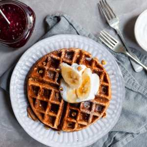 Vegan Banana Waffle on breakfast table served with fresh bananas and maple syrup