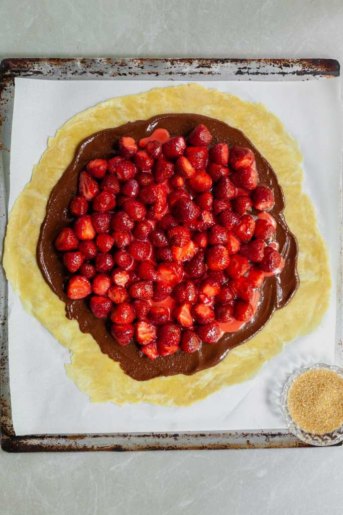 Galette pastry rolled out with hazelnut chocolate spread and fresh strawberries on top just before folding the crust and baking