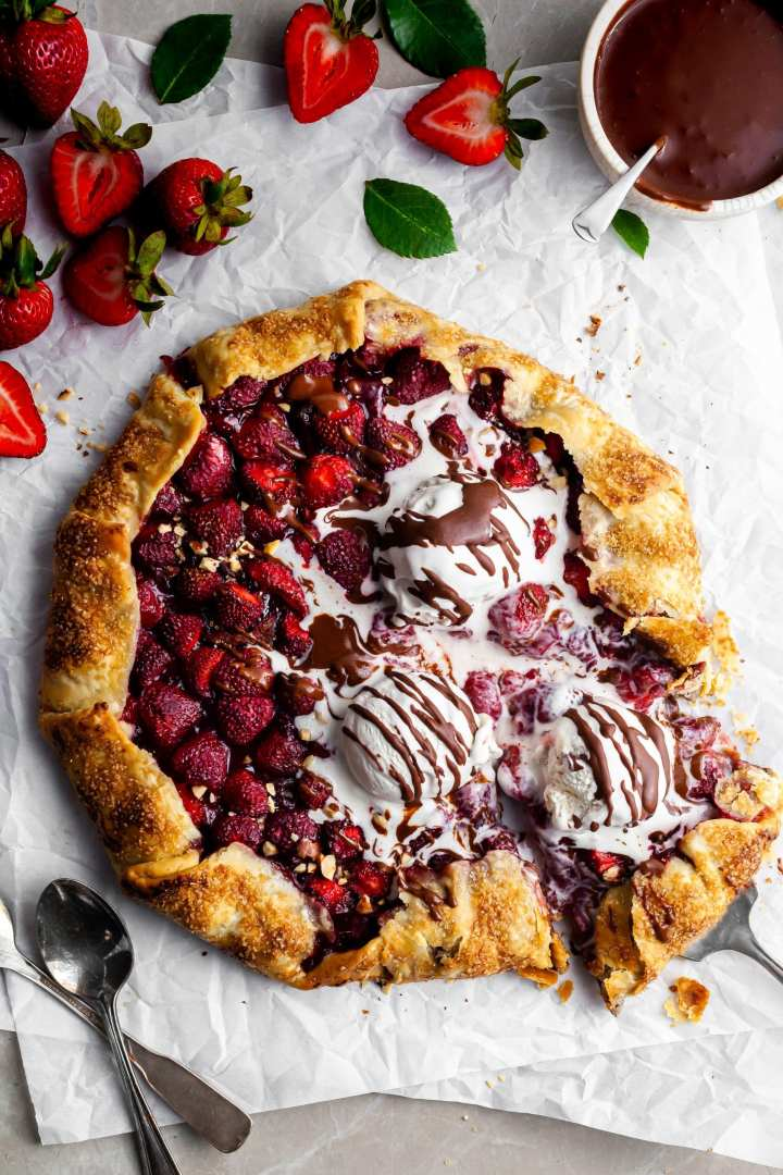 Fresh Strawberry Galette with Hazelnut Chocolate Cream warm from the oven with three scoops of plant-based vanilla ice cream and a drizzle of chocolate sauce