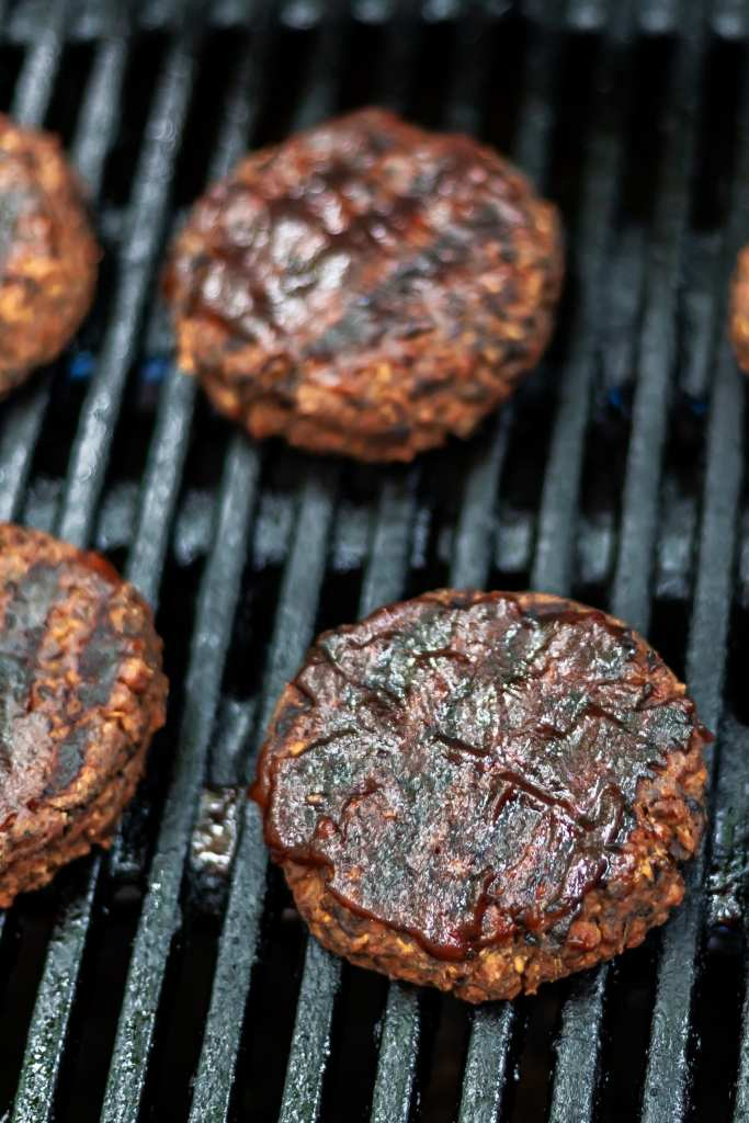 Veggie burgers on grills with grill marks and barbecue sauce