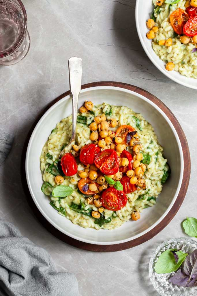 2 bowls of risotto topped with roasted tomatoes and chickpeas