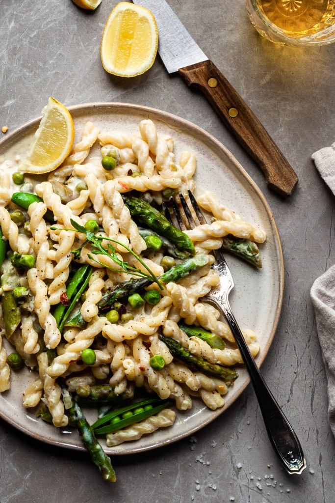 Flay lay of a plate of creamy vegan lemon pasta with asparagus and peas. A slice of lemon sits beside the plat and a glass of wine