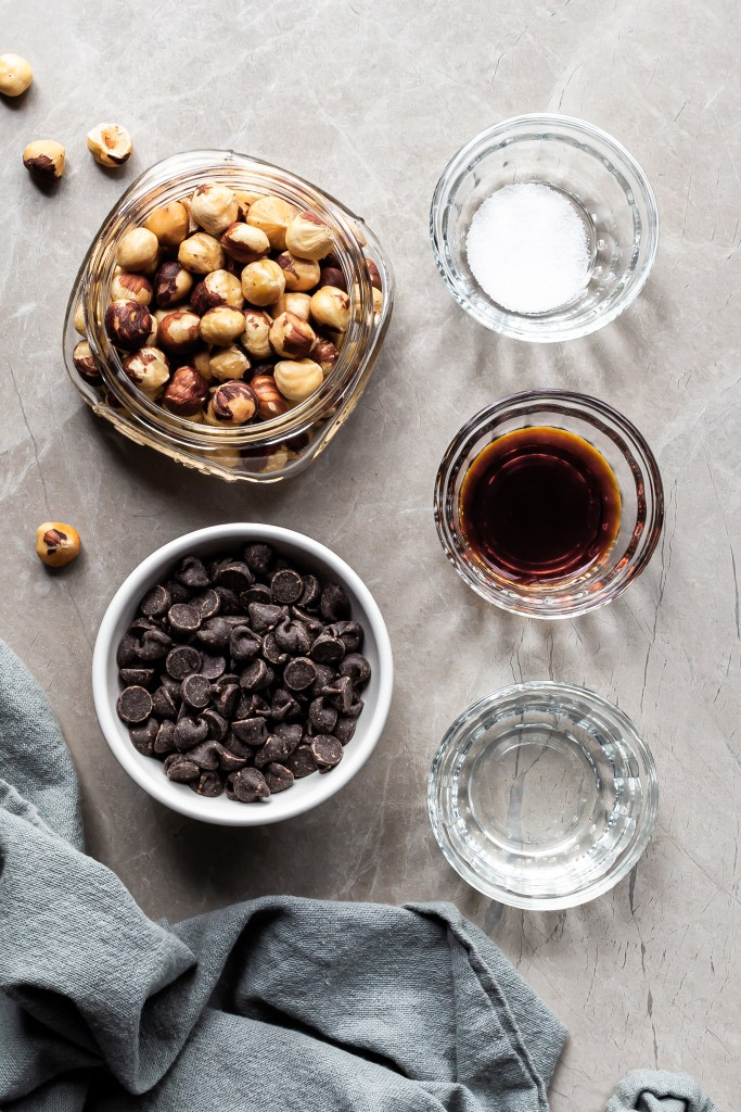 Ingredients measured out for the homemade nutella in small glass bowls: chocolate chips, hazelnuts, vanilla, salt and coconut oil