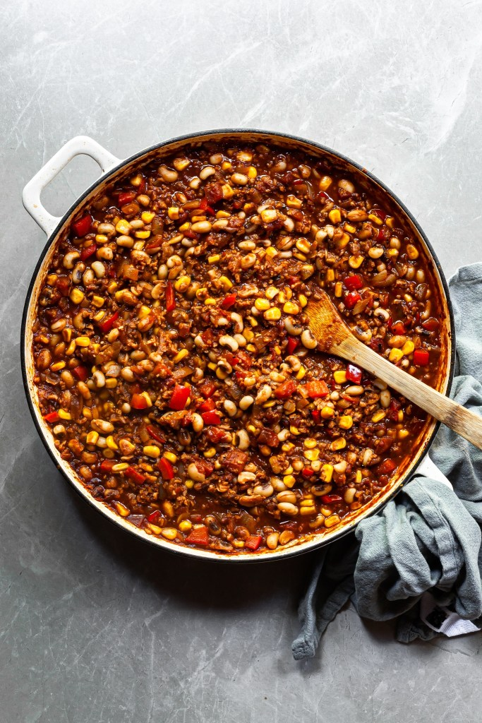 White enameled skillet full of black-eyed pea and corn chili