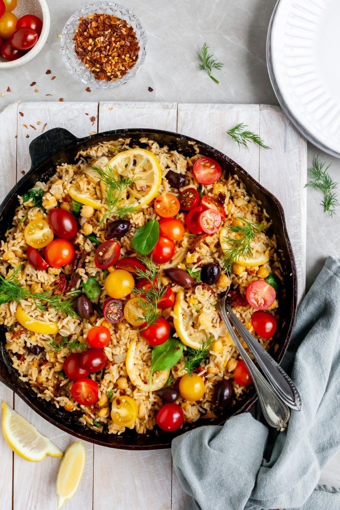 Cast iron skillet filled with Greek rice, cherry tomatoes, black olives and lemon slices
