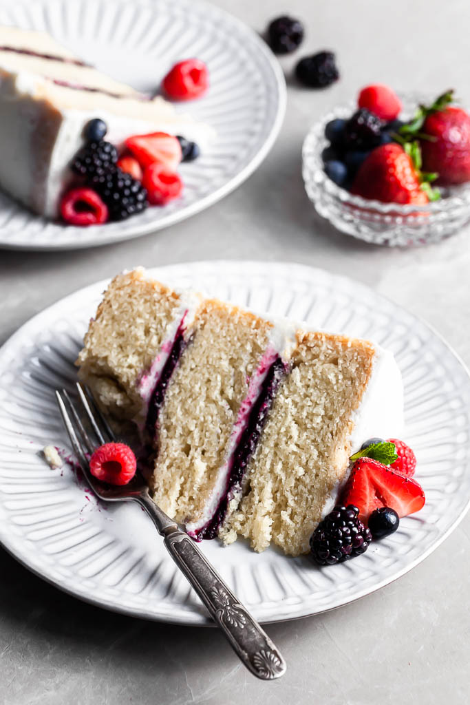 Slice of berry vanilla cake on a white plate with a fork, and a bite missing