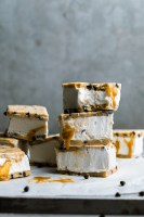 a stack of chocolate chip cookie dough ice cream sandwiches dripping with caramel