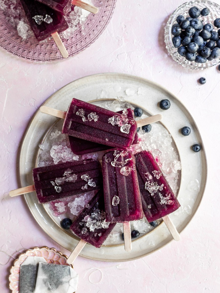 a cream colored plate covered in crushed ice with purple popsicles and blueberries resting on top