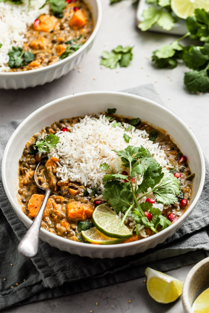 White bowl filled with sweet potato lentil curry garnished with cilantro, slices of lime, and pomegranate arils