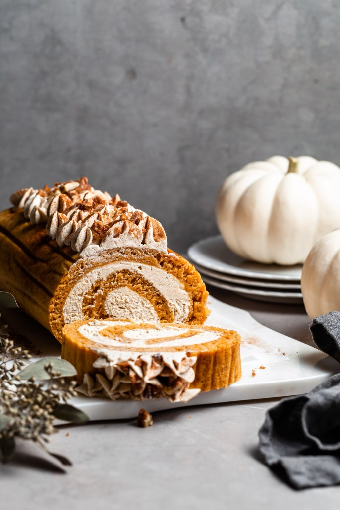 pumpkin swiss roll on a white platter with a single slice cut