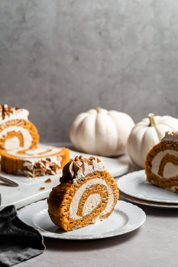 Slices of pumpkin roll on white plates in the foreground and the sliced pumpkin roll in the background